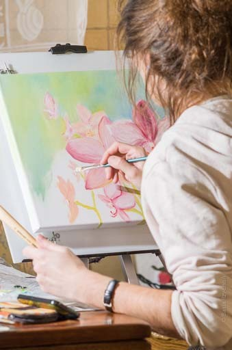 Basia Rzychoń maluje obraz z kwiatami do salonu.