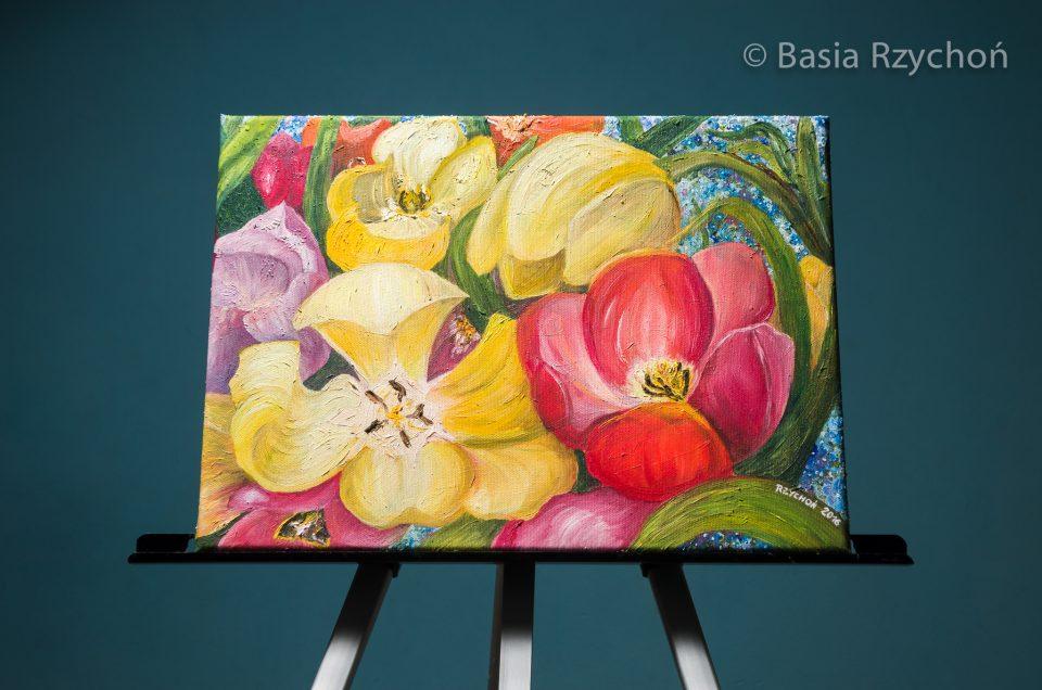 """Obraz olejny (w tym przypadku """"Tulipany"""" (olej na płótnie, 40 x 30 cm, B. Rzychoń 2016) wyeksponowany na sztaludze. Ciemna ściana w tle robi robotę, im większa odległość tym efekt jest lepszy."""